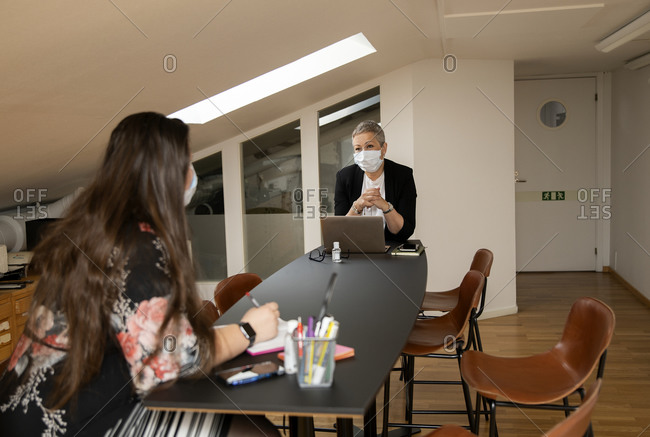 Female coworkers with protective face masks talking in office