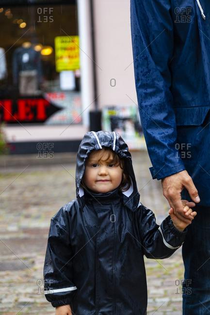 Girl wearing rain coat holding fathers hand