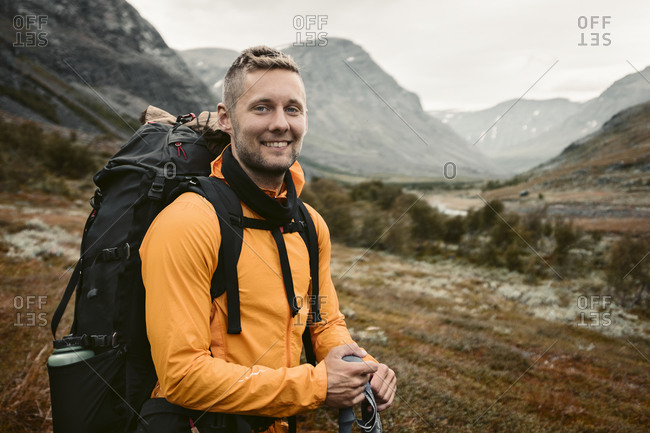 Smiling man carrying backpack in mountains
