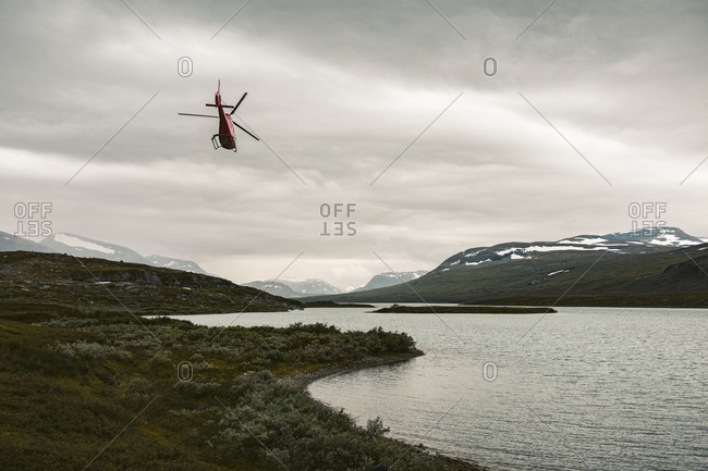 Helicopter over lake in mountains. Detailed shot.