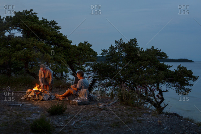Couple relaxing at log fire. Detailed shot.