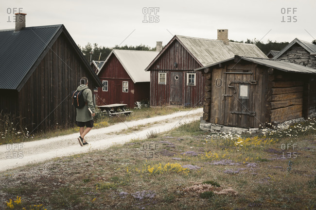 Man on dirt road leading to wooden houses