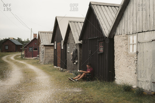 Man sitting in front of wooden house