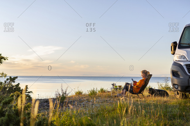 Woman relaxing on lounge chair at sea