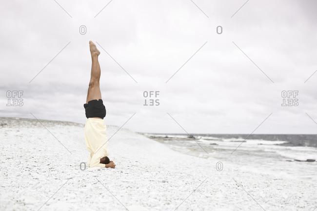 Man doing handstand on sandy beach