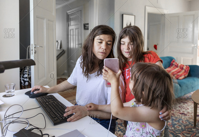 Mother and daughters looking at cell phone