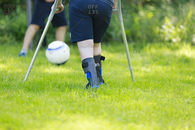Low section of child using crutches playing football