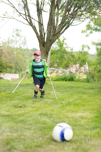 Boy playing football in garden. Detailed shot.