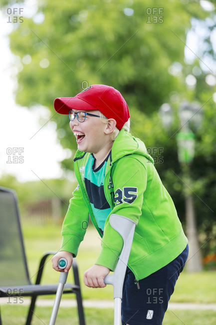 Happy boy in garden using crutch