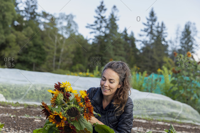 Smiling woman holding bunch of sunflowers