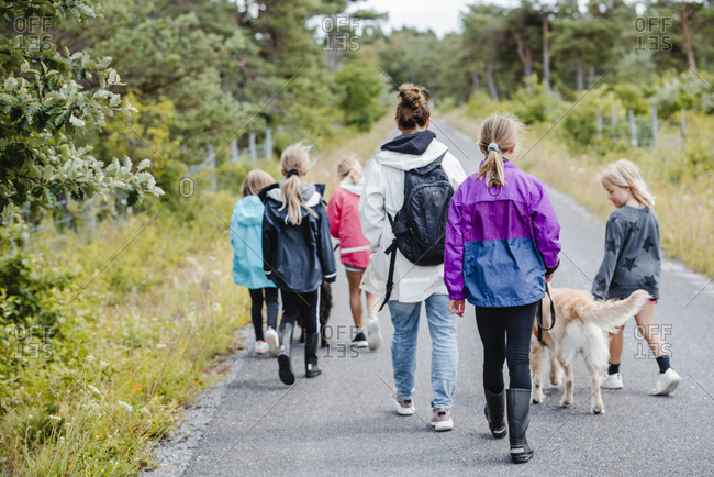 Mother and daughters walking at country road