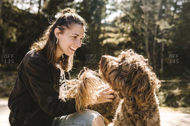 Smiling woman stroking dog. Detailed shot.