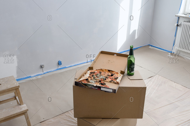 Beer bottle and pizza on top of cardboard boxes