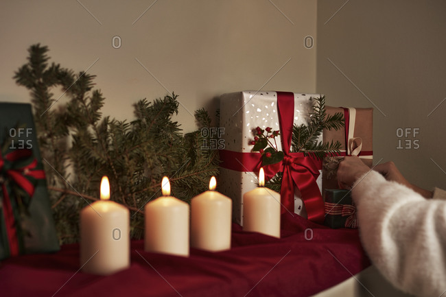 Hand putting Christmas presents on shelf