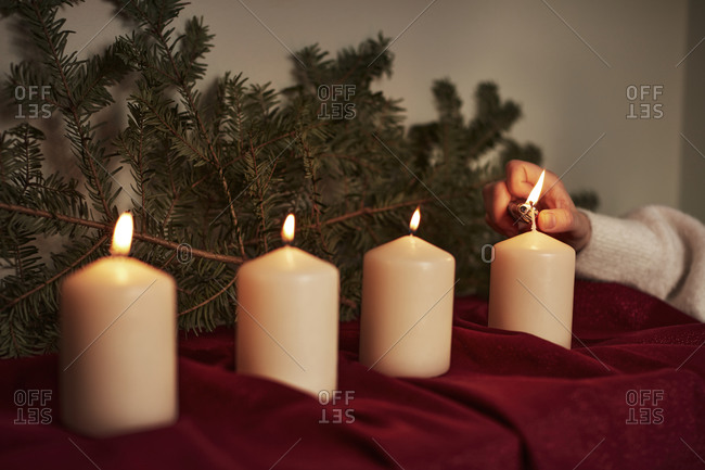 Hand lighting Advent candle. Detailed shot.