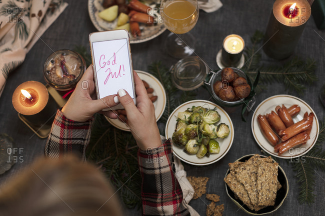 Hands holding cell phone with Christmas greeting over Christmas table