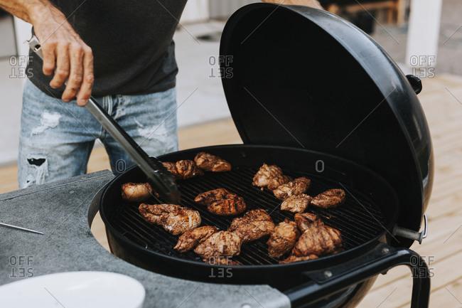 Man preparing meat on barbecue. Detailed shot.