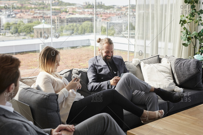 Coworkers using cell phones on sofa