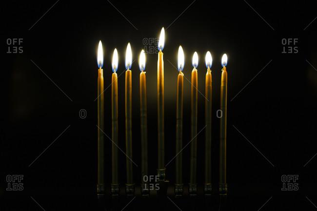 Lit Golden Hanukah Candles in Dark Room
