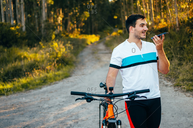 Smiling young man with cell phone pushing bicycle