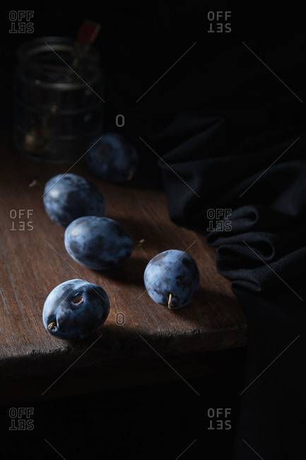 Blue plum on a wooden table against the background of a glass jar
