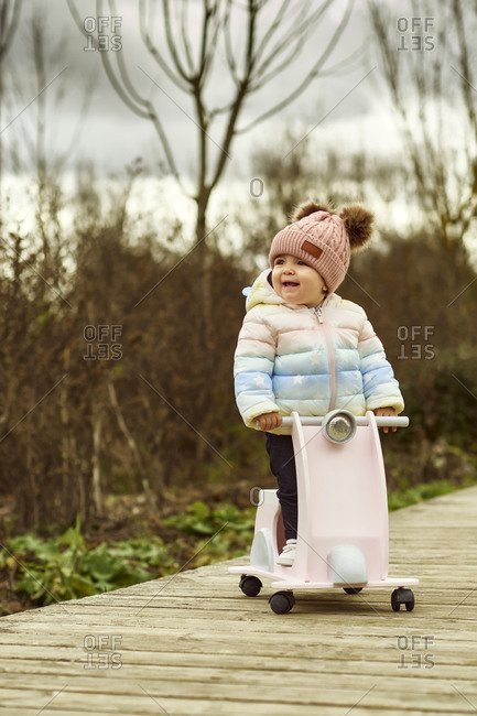 A 1 year old baby girl is with a pink motorcycle outside