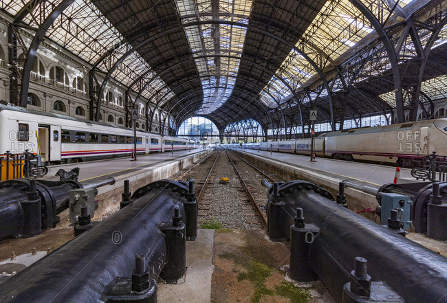 Barcelona, Spain - December 21, 2019: Trains on the platforms of a Barcelona station with a glass roof