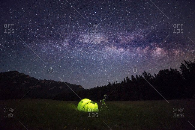 Camping tent at night against amazing sky full of stars and milky-way