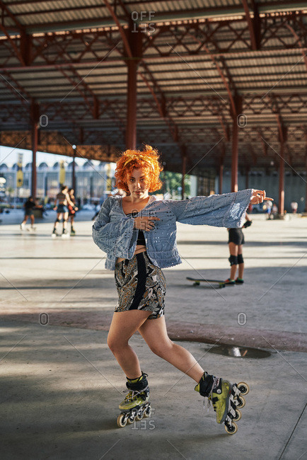 Young alternative redhead dancing in roller skates inside a hangar