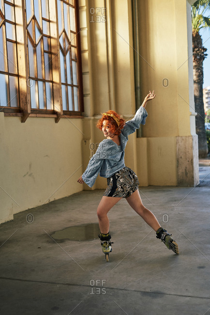 Young alternative redhead girl dancing in roller skates