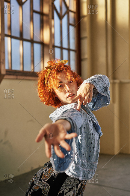 Young alternative redhead girl dancing in a blue blouse