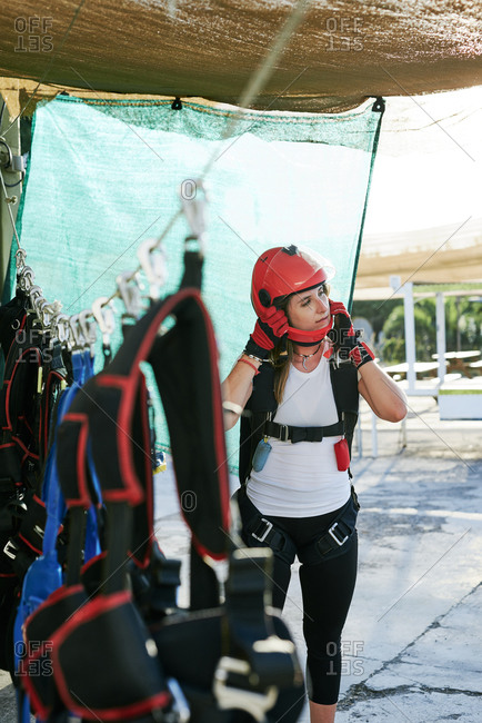 Young female skydiver with parachute backpack, gloves and helmet