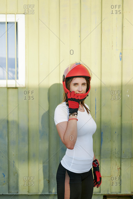Young fit female posing with a red helmet and red gloves