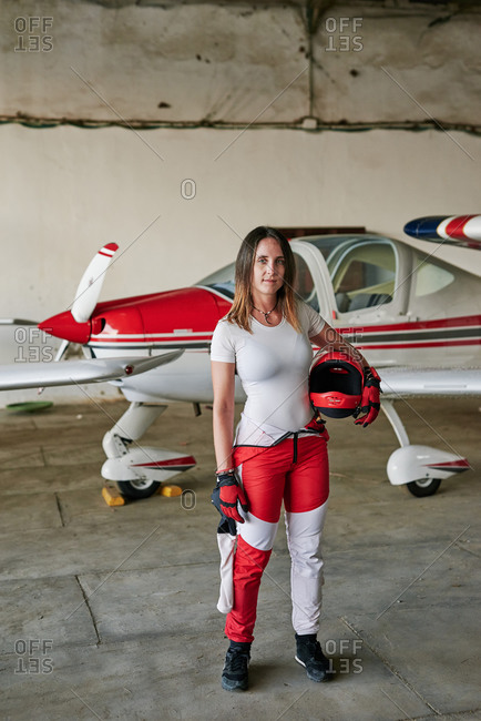 Young female skydiver in a plane hangar with a helmet