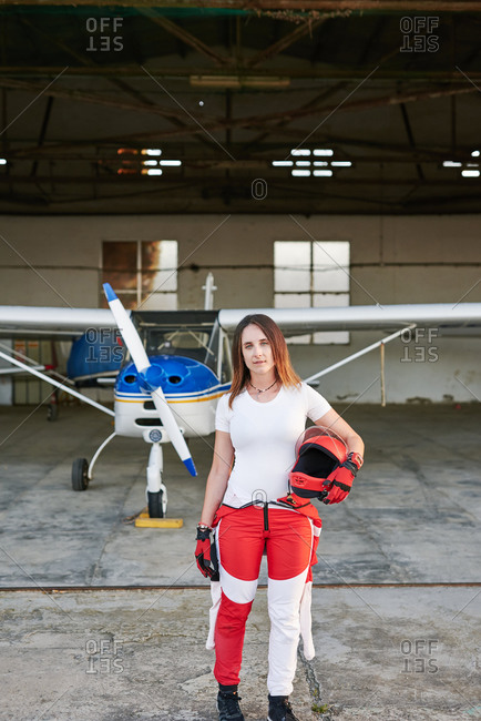 Young female skydiver in a plane hangar with a plane behind her