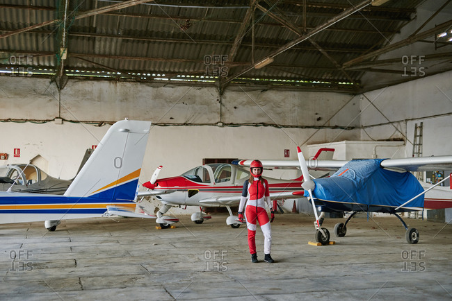 Young female skydiver in a plane hangar surrounded by planes
