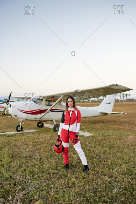 Young female skydiver in an airfield with a plane behind her