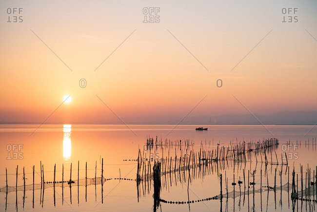 Boat and fishing nets at Valencia's Albufera sunset against the light