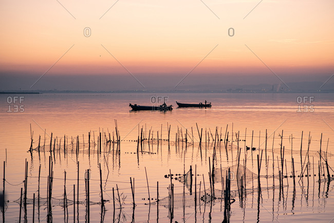 Two boats and fishing nets at the Albufera sunset against the light