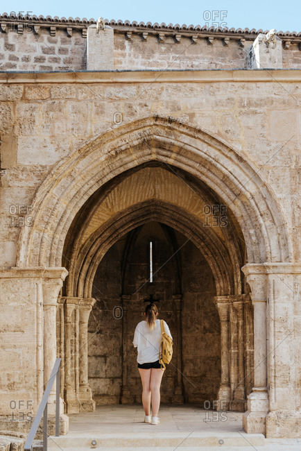 Girl looking at a church's arch with a backpack
