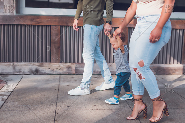 Family of three playing in Downtown, parents holding baby boy's hands