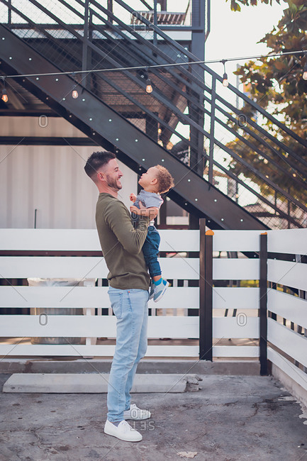 Dad laughing while holding boy in front of white fence and black steps