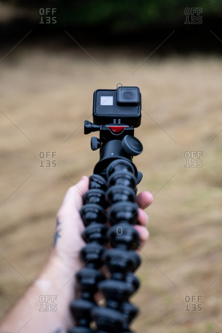 Hand holding tripod with action camera over brown grass in field