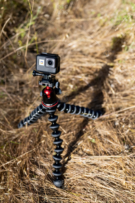 Small action camera mounted on tripod in bright sunshine in field