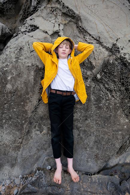 Full body portrait of tween lying on coastal stones with eyes closed