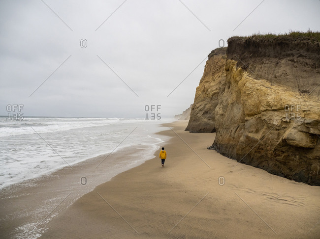 Lone young person walking along deserted California beach on gray day
