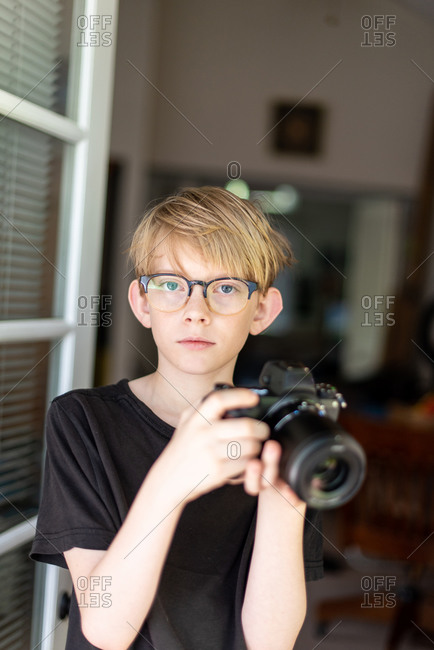 Tween making eye contact holding modern camera in doorway to home