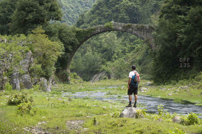 One man standing on a rock under an ancient bridge on a river