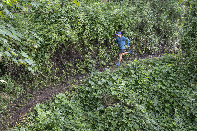 One man running down on a trail surrounded by vegetation in Zacatlan