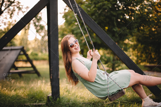 Happy young woman swinging in park during summer